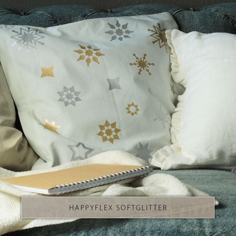 Heller Kissenbezug mit goldenen und silbernen Sternen aus HappyFlex Softglitter bedruckt.