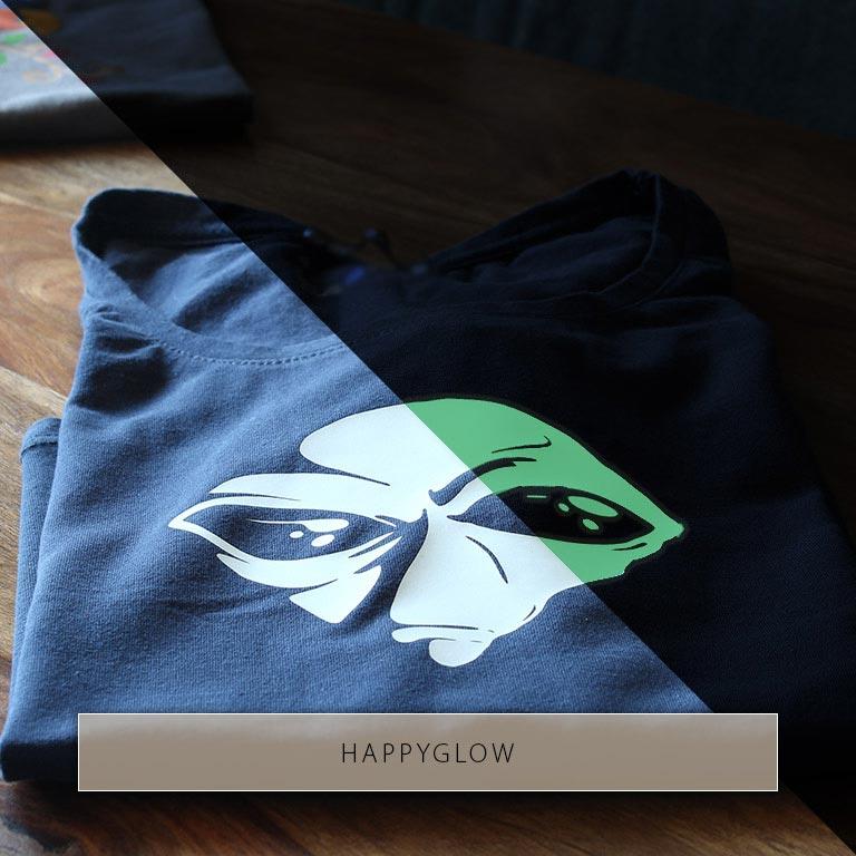 Zweigeteiltes Bild, dass den Kopf eines Aliens, der auf ein schwarzes T-Shirt gedruckt wurde, einmal bei Licht und einmal leuchtend im Dunkeln zeigt.
