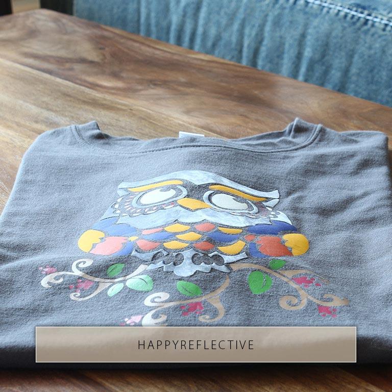 Bunte Eule mit reflektierenden Elementen auf T-Shirt gedruckt.